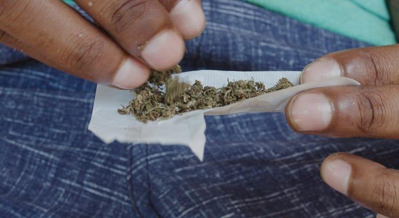 A man fills and rolls a marijuana joint