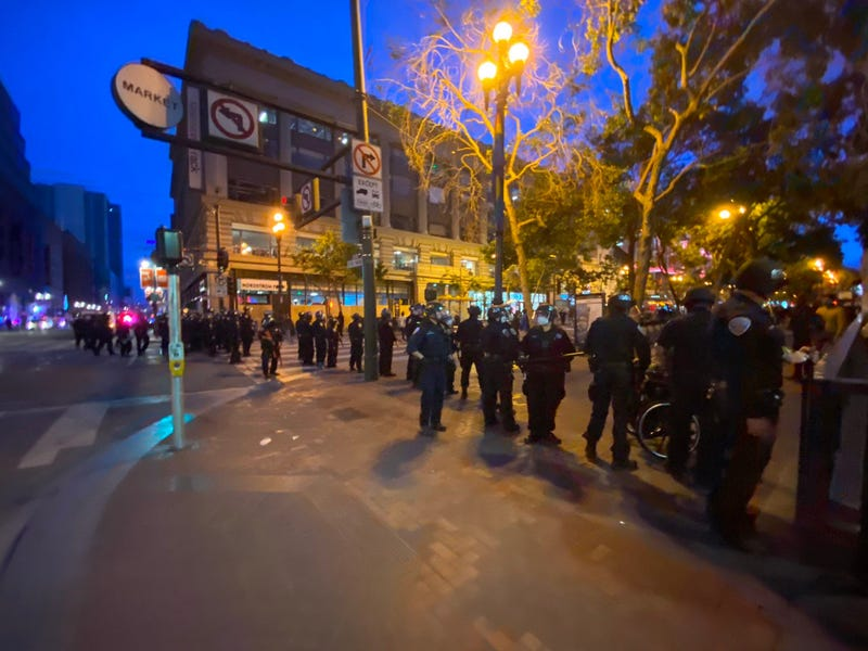Police stand on Market St. In San Francisco as looters hit stores along the strip.