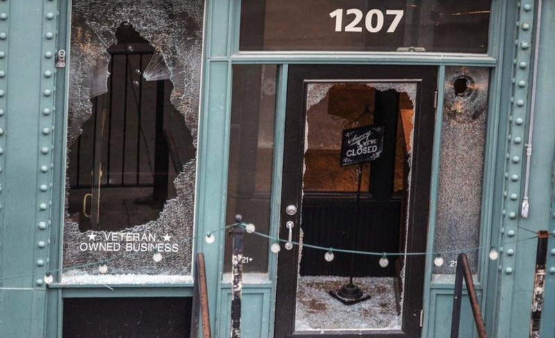 """A """"sorry we're closed"""" sign sits in the entrance surrounded by broken glass at The Hive, near where a man was shot to death during protests in May 20202. CHRIS MACHIAN/OMAHA WORLD-HERALD VIA AP"""