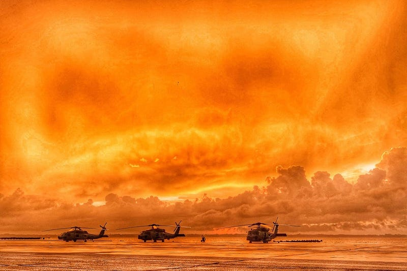 Three MH-60R Sea Hawk helicopters line the seawall as the sun rises over the St. Johns River at Naval Air Station Jacksonville, Fla.