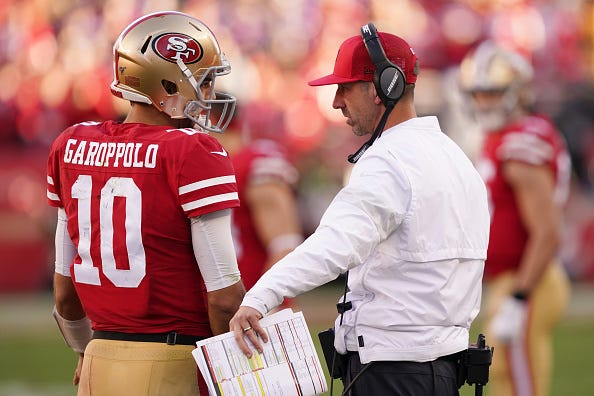 Kyle Shanahan and Jimmy Garoppolo talk on the sideline.