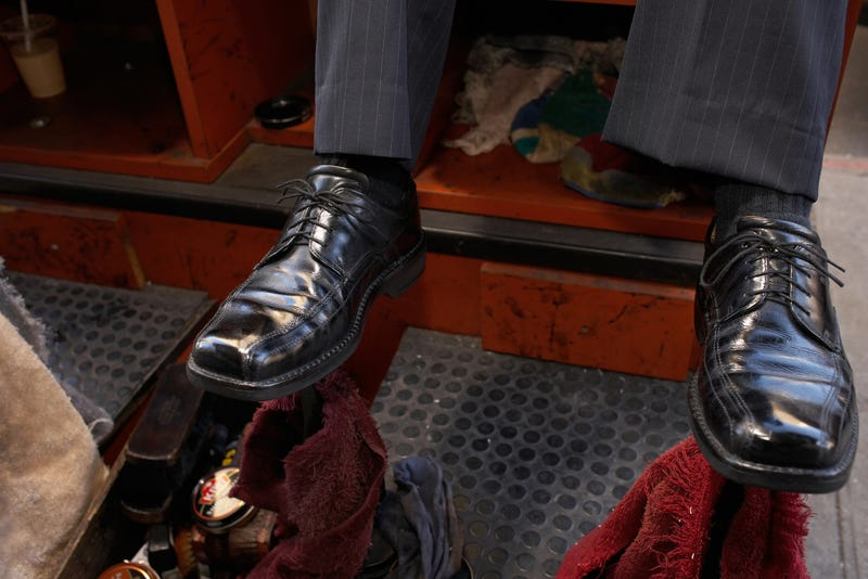 A man wearing a pair of black dress shoes sits at a shoe shine stand