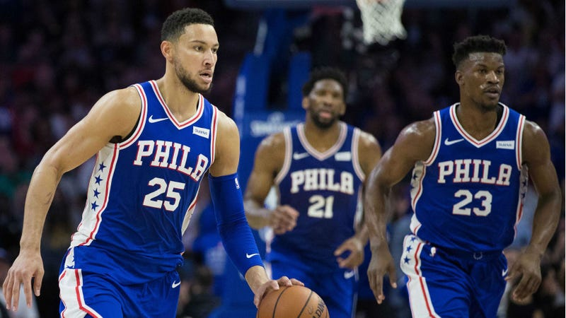 Philadelphia 76ers guard Ben Simmons (25) dribbles up court in front of guard Jimmy Butler (23) and center Joel Embiid (21) during the second quarter against the Boston Celtics at Wells Fargo Center.