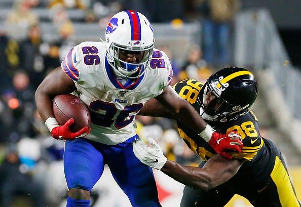 Bills RB Devin Singletary stiff arms a Steelers tackler.