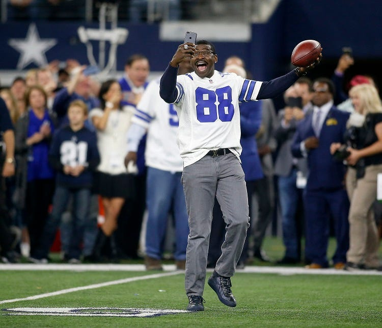 Former Dallas Cowboys receiver Michael Irvin (88) takes a selfie video as he was one of several players introduced from the 1992 Super Bowl team before the first half of a game against the Philadelphia Eagles on Sunday, Nov. 19, 2017 at AT&T Stadium in Ar