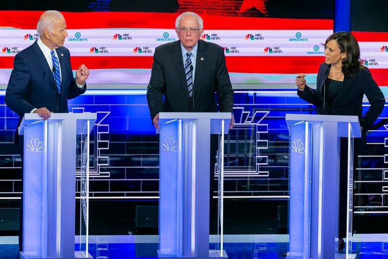 Sen. Kamala Harris (D-Calif.), right, speaks to former Vice President Joe Biden, left, as Sen. Bernie Sanders (I-Vt.) l