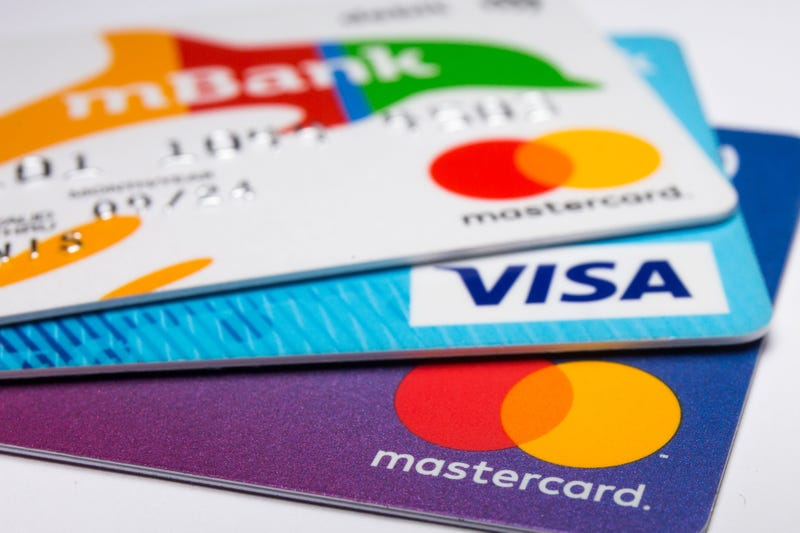 n this photo illustration a Visa credit card and Mastercard debit cards are seen displayed.
