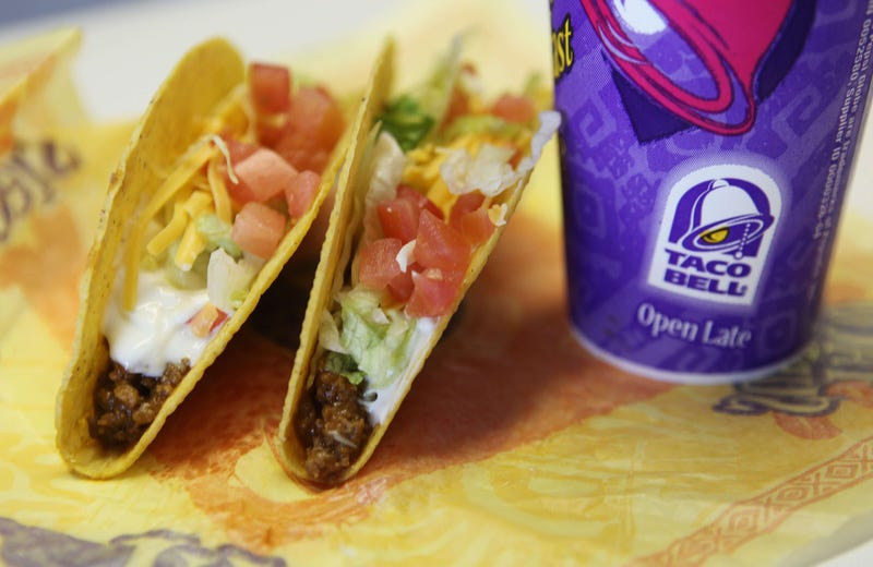 Two hard shell tacos leaning against a soda cup bearing the Taco Bell logo