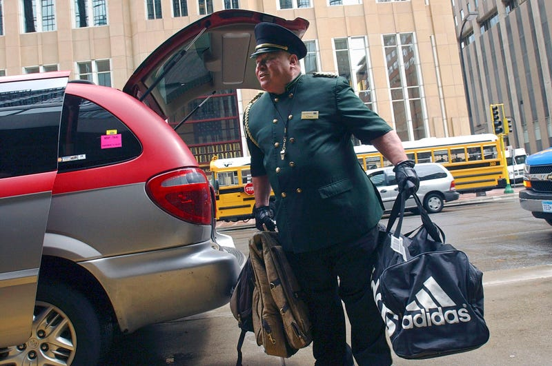 A doorman carries bags from the trunk of a mini van