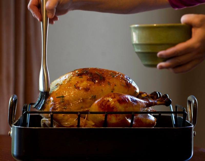 An unseen cook brushes a roast turkey with oil