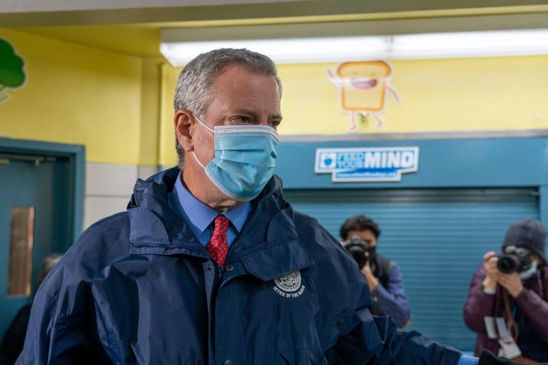 Mayor Bill de Blasio greets staff workers at a polling site in Manhattan.