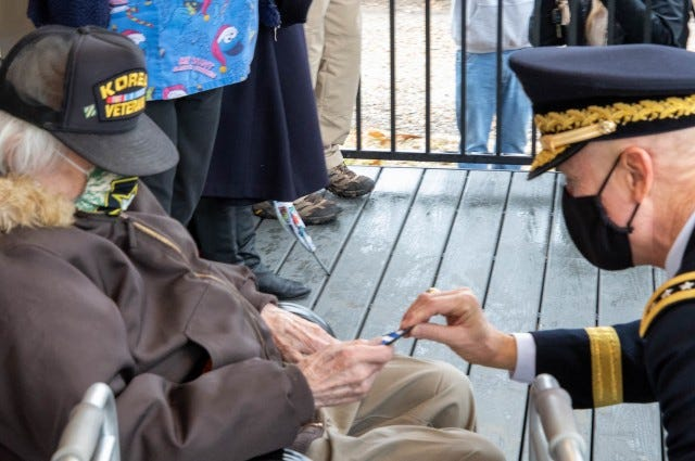 Korean War veteran J.P. Whitaker receives a 3rd Infantry Division patch from First Army Commanding General, Lt. Gen. Thomas James Jr., during a ceremony welcoming Whitaker back to his refurbished home in Davenport, Iowa.