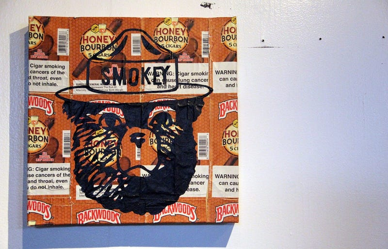 A painting of Smokey the Bear over plastered Backwoods wrappers at the TRAP CHAPEL pop-up art gallery in Atlanta