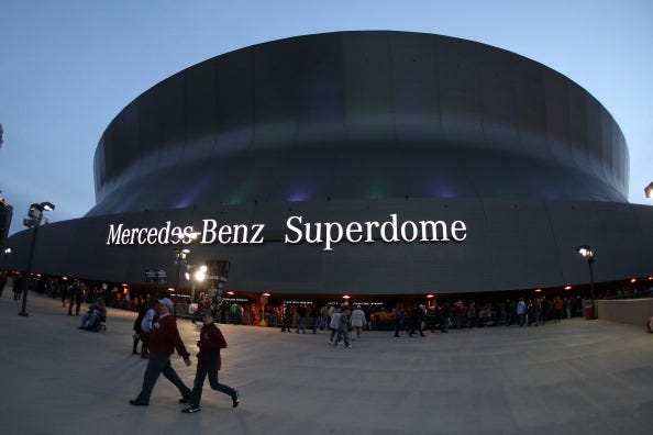 Fans walk by the Mercedes-Benz Superdome