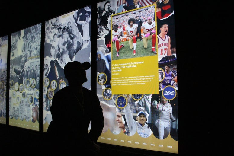 Big Tigger kneels in front of a social justice exhibit at the NFL Experience during the week of Super Bowl 53 in Atlanta