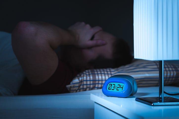 Man awake with clock reading 3am