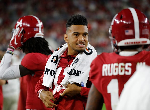 Tua Tagovailoa chats with his teammates on the Alabama sidelines