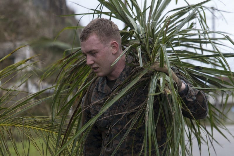 A Marine from the 31st Marine Expeditionary Unit cleans up debris after Typhoon Mangkhut