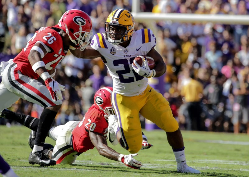 Oct 13, 2018; Baton Rouge, LA, USA; LSU Tigers running back Clyde Edwards-Helaire (22) break away from Georgia Bulldogs defensive back Tyrique McGhee (26) and defensive back J.R. Reed (20) during the second quarter at Tiger Stadium. Mandatory Credit: Deri