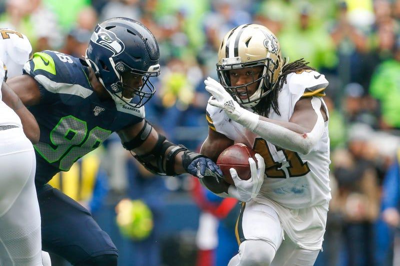 New Orleans Saints running back Alvin Kamara (41) rushes against Seattle Seahawks defensive end Rasheem Green (98) during the fourth quarter at CenturyLink Field.