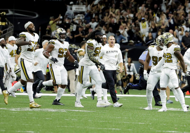 New Orleans Saints outside linebacker Demario Davis (56) and quarterback Drew Brees (center) celebrate after a 12-10 win against the Dallas Cowboys at the Mercedes-Benz Superdome.