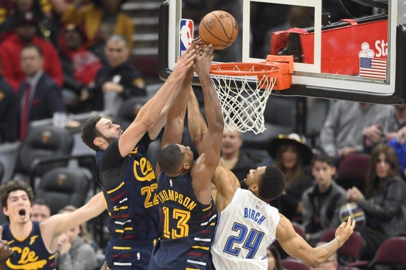 Nov 27, 2019; Cleveland, OH, USA; Cleveland Cavaliers forward Larry Nance Jr. (22) and center Tristan Thompson (13) reach for a rebound beside Orlando Magic center Khem Birch (24) in the fourth quarter at Rocket Mortgage FieldHouse. Mandatory Credit: Davi