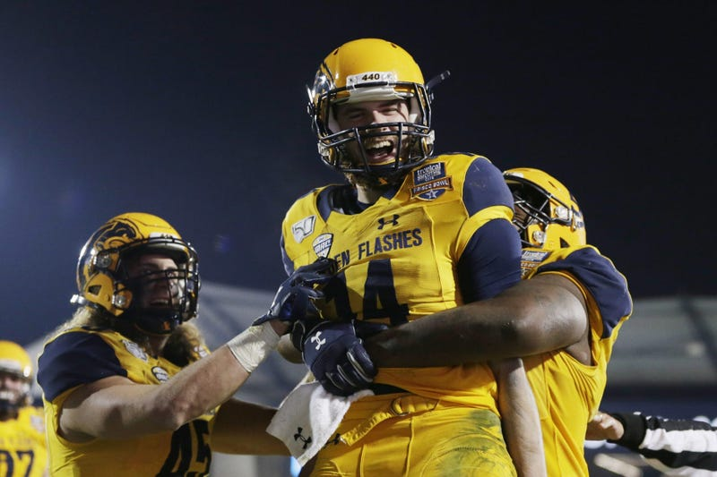 Kent State Golden Flashes quarterback Dustin Crum (14) celebrates a touchdown with offensive lineman Julian Sams (55) in the fourth quarter against the Utah State Aggies during the Frisco Bowl at Toyota Stadium.