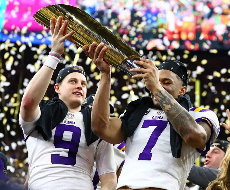 LSU Tigers safety Grant Delpit (7) hoists the national championship trophy with quarterback Joe Burrow (9) after a victory against the Clemson Tigers in the College Football Playoff national championship game at Mercedes-Benz Superdome.