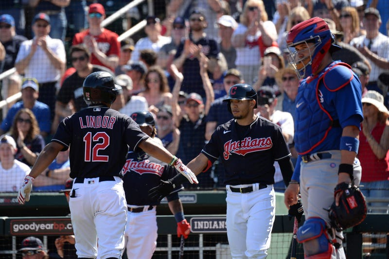 Cleveland Indians shortstop Francisco Lindor (12) slaps hands with Cleveland Indians second baseman Cesar Hernandez (7) after hitting a solo home run against the Chicago Cubs during the first inning of a spring training game at Goodyear Ballpark.