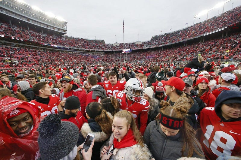 Ohio State Buckeyes players wade through the fans who rushed the field following their 28-17 win over the Penn State Nittany Lions on Nov. 23. The amount of money brought in by the football program pays for most of the university s other sports