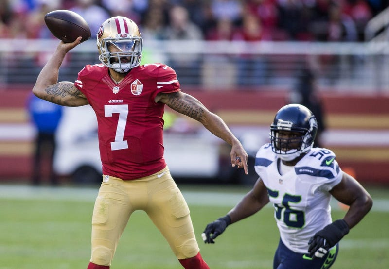 San Francisco 49ers quarterback Colin Kaepernick (7) passes the football while being rushed by Seattle Seahawks defensive end Cliff Avril (56) during the first quarter at Levis Stadium.