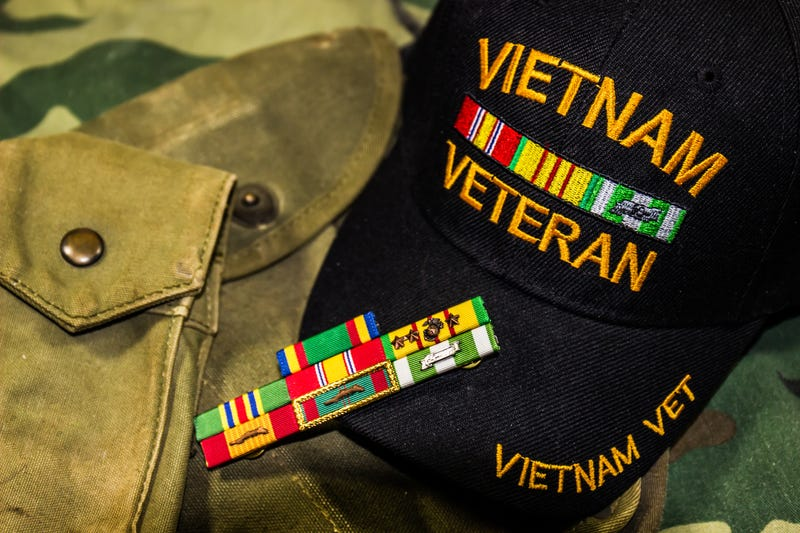 Vietnam Veterans hat, service ribbons and pouches on camouflage uniform