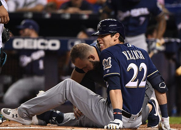 Brewers slugger Christian Yelich grimaces after fouling a ball off his kneecap.