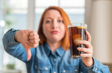Girl Holding Soda Giving Thumbs Down