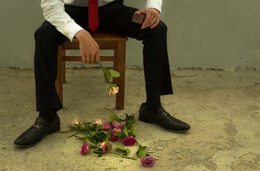 Sad Groom With Flowers At Feet