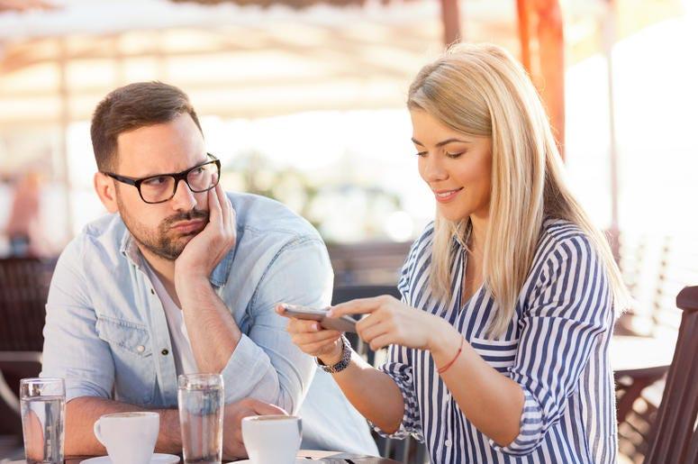 Man looking at woman using dating app