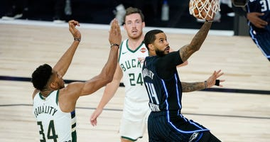 Aug 24, 2020; Lake Buena Vista, Florida, USA; Orlando Magic's D.J. Augustin (14) drives to the basket ahead of Milwaukee Bucks' Giannis Antetokounmpo (34) during the first half in game four of the first round of the 2020 NBA Playoffs at The Field House. M