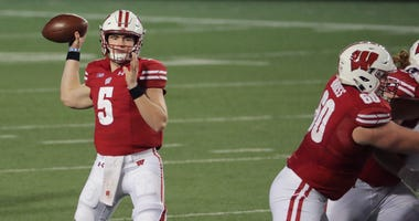 Wisconsin quarterback Graham Mertz looks and completes one of his 20 completed passes Friday night. Mertz only threw one incompletion and threw four of his five touchdowns in the first half in Wisconsin's opening victory over Illinois, Uwgrid24 18