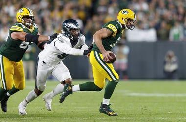 Aaron Rodgers (12) evades pressure from Philadelphia Eagles defensive end Derek Barnett