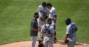 Members of the Marlins gather at the mound