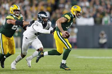 Aaron Rodgers (12) evades pressure from Philadelphia Eagles defensive end Derek Barnett