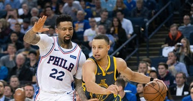 Warriors guard Stephen Curry dribbles past 76ers forward Wilson Chandler