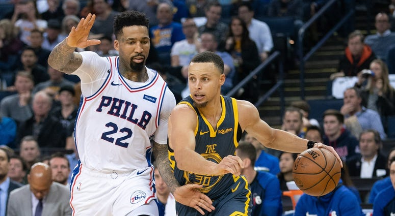 Warriors guard Stephen Curry dribbles past 76ers forward Wilson Chandler