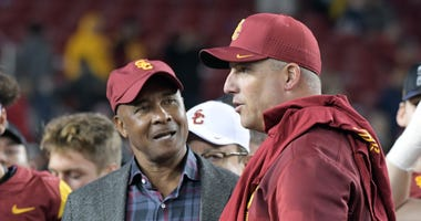 Southern California Trojans athletic director Lynn Swann (left) talks with head coach Clay Helton after the Pac-12 Conference championship game against the Stanford Cardinal at Levi's Stadium