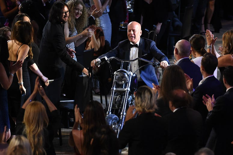 "LOS ANGELES - JULY 14: Bruce Willis enters on a motorcycle at the ""Comedy Central Roast of Bruce Willis"" at the Hollywood Palladium on July 14, 2018 in Los Angeles, California."