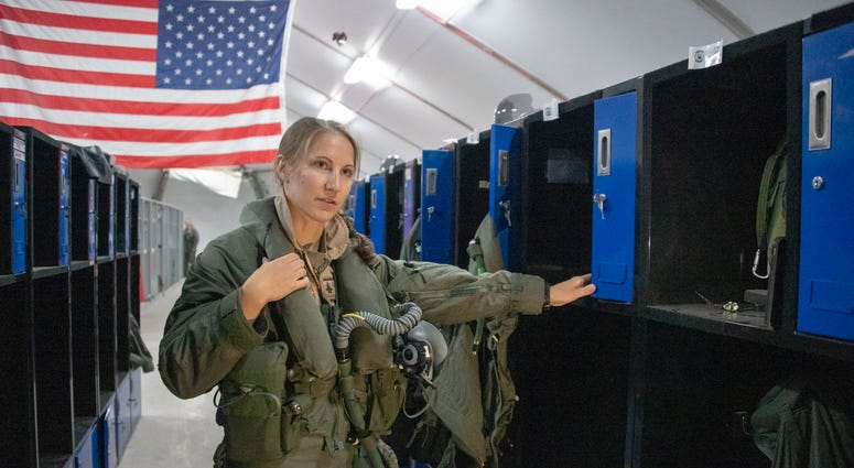 U.S. Air Force Capt. Emily Thompson, 421st Expeditionary Fighter Squadron pilot, dons flight equipment