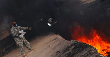 Master Sgt. Darryl Sterling, 332nd Expeditionary Logistics Readiness Squadron equipment manager, tosses unserviceable uniform items into a burn pit, March 10, 2008.