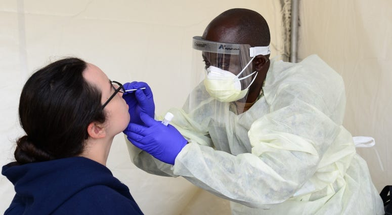 Hospital Corpsman 3rd Class Rene Azombi, a Navy reservist temporarily assigned to Navy Medicine Readiness and Training Command Great Lakes (NMRTC) to assist with COVID-19 screening efforts, conducts a nasal swab on a recruit.