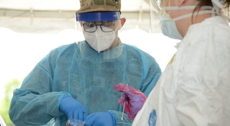 "U.S. Air National Guard Senior Airman Manuel Zertuche 185th Air Refueling Wing medical technician works with medical staff in order to administer a COVID-19 test at the Sioux Center, Iowa ""TestIowa"" test site on May 27, 2020."