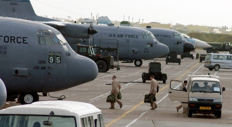 C-130 Hercules aircrew members board their aircraft for an Operation Enduring Freedom mission at Karshi-Khanabad Air Base, Uzbekistan, on April 19, 2005.